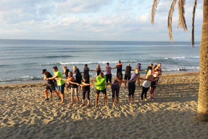 Gemeinsames Stretching am Strand von Marbella